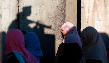 Palestinians wait to cross the Qalandia checkpoint between the West Bank city of Ramallah and Jerusalem as they head to Jerusalem's Al-Aqsa Mosque for the first Friday prayers of Ramadan. June 2, 2017.