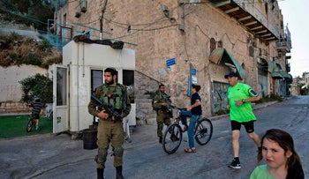 Israeli soldiers keeping guard as Israeli children play outside the Beit Hadassah settlement in the West Bank city of Hebron, May 29, 2017.