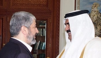 FILE PHOTO: A handout picture released by the Qatari News Agency (QNA) shows Qatari Emir Hamad bin Khalifa al-Thani (R) welcoming Palestinian exiled Hamas leader Khaled Meshaal in Doha on January 10, 2010.