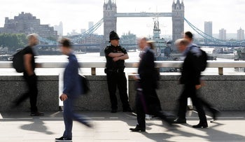 Commuters rush past a City of London police officer on London Bridge after is was reopened following Saturday's attack, London, June 5, 2017.