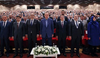 Turkey's President Recep Tayyip Erdogan, center, stands as he listens to the national anthem, prior of delivering a speech at a conference in Istanbul, Saturday, April 29, 2017.