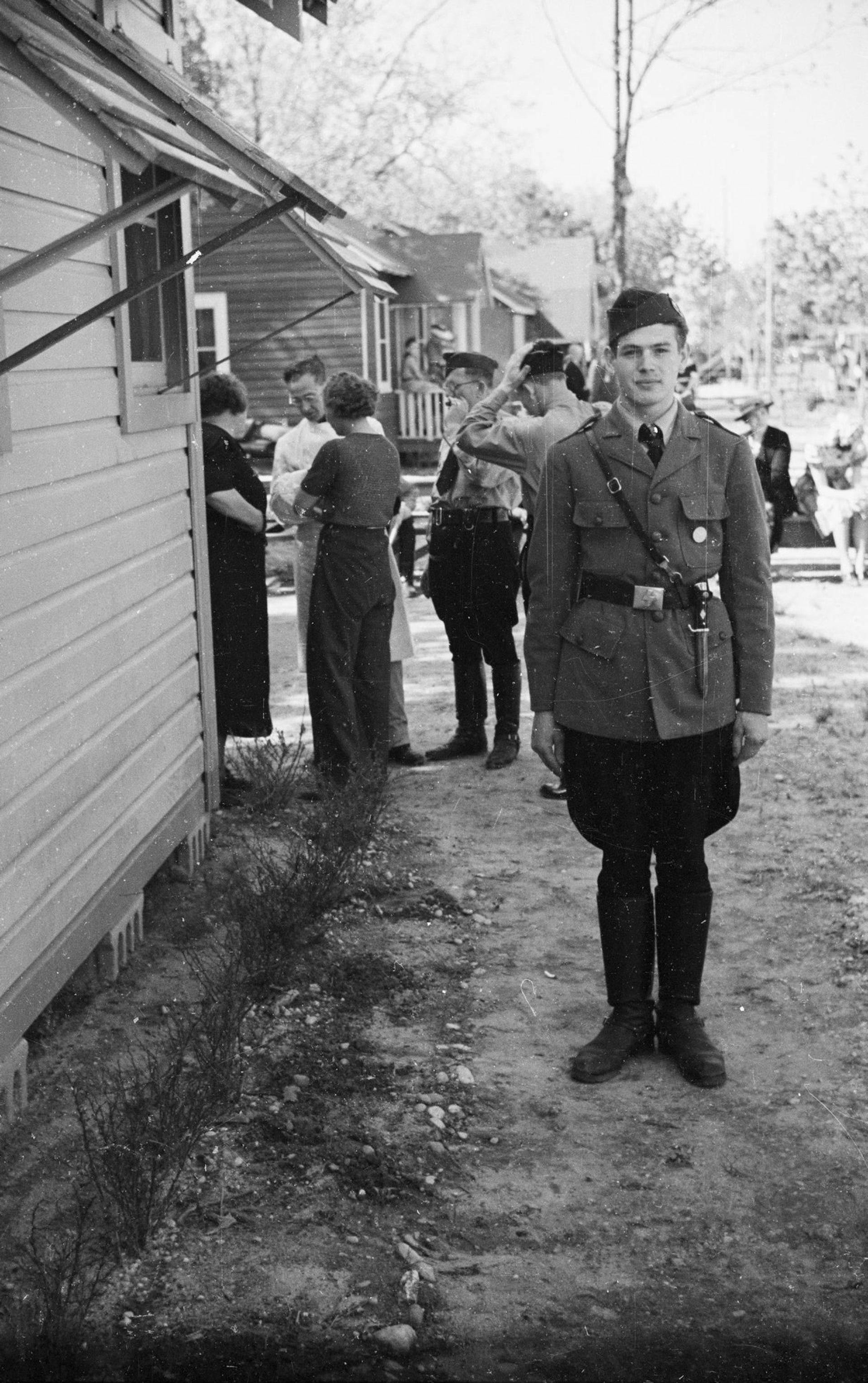 In this May 22,1938 photo provided by the New York City Municipal Archives, a young member of the German American Bund poses for a photo with other members gathered behind him, at Camp Siegfried in Yaphank, N.Y.
