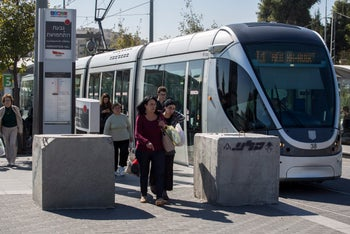 File photo: Concrete blocks are a common sight along Israel's roads. Here blocks were installed to prevent car ramming attacks from a busy road adjacent to Jerusalem's light-rail line.