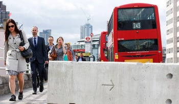 Commuters walk past a concrete barrier, erected following Saturday night's terror attack, in London, U.K., on Monday, June 5, 2017