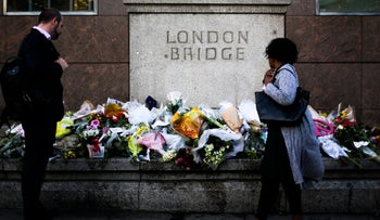 People look at the floral tributes placed at London Bridge to commemorate the victims of Saturday's attack in London, Tuesday, June 6, 2017.