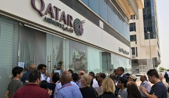 People gather outside a branch of Qatar Airways in the United Arab Emirate of Abu Dhabi, June 6, 2017.