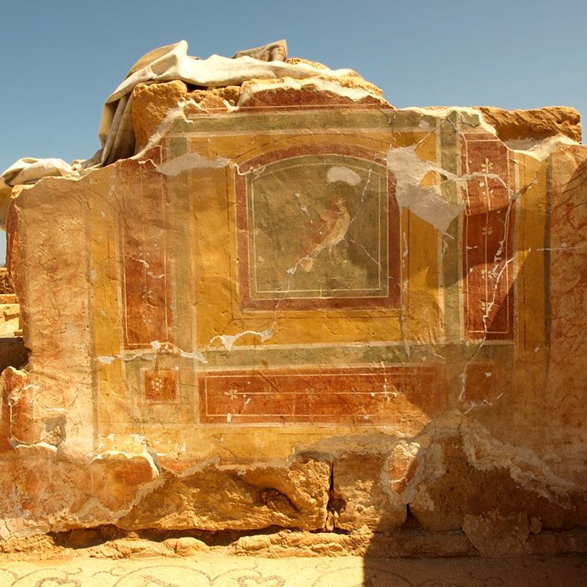 Fresco in 1,700-year-old Roman villa in Ptolemais: Photo shows ruins of plastered wall in Ptolemais, on which a picture was painted, and framed with ocher and brick-red painted rectangles. In the foreground we see the edge of an elaborate mosaic.