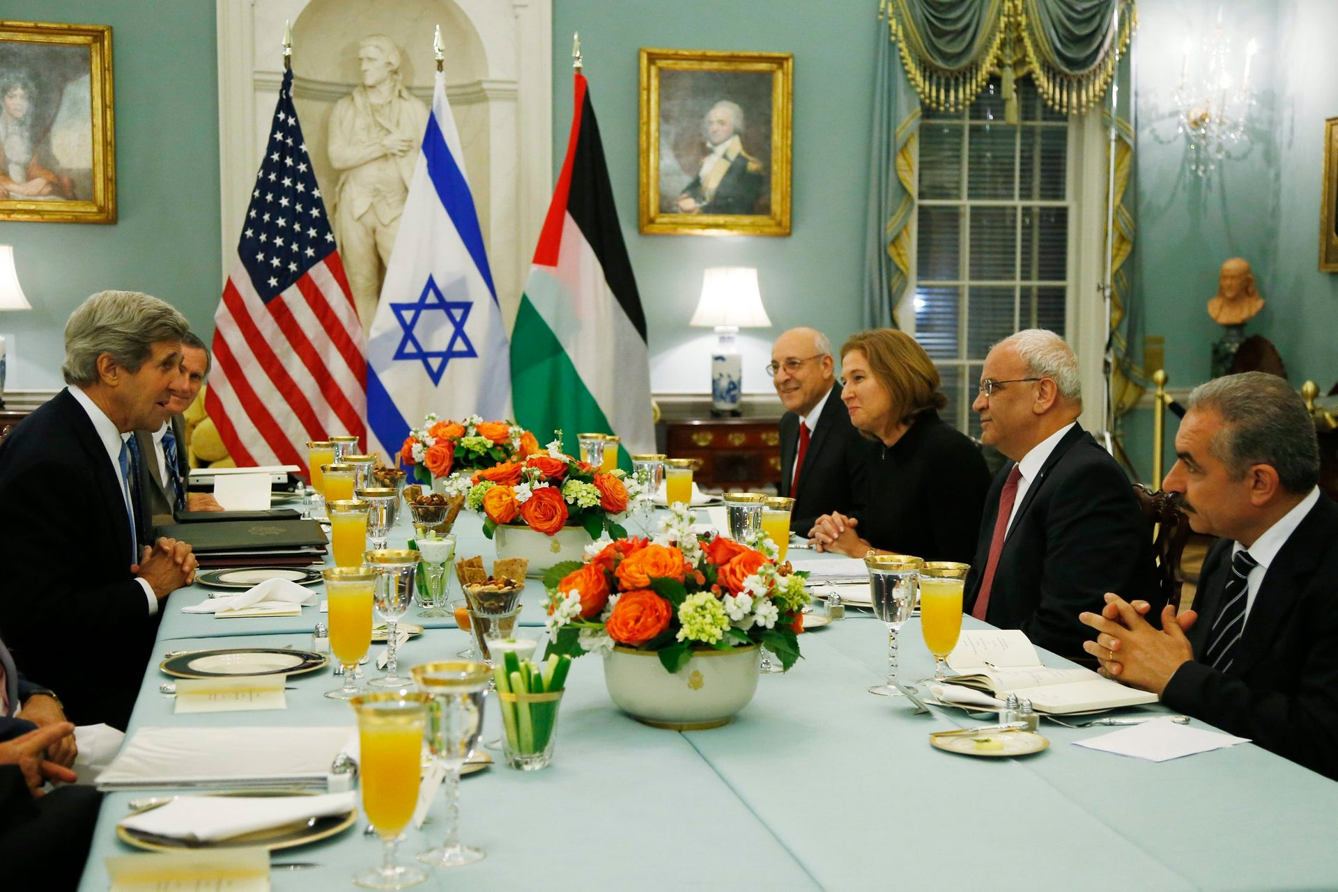Then-U.S. Secretary of State John Kerry, left, sits across from Israeli and Palestinian negotiators at an Iftar celebration in Washington, July 2013.