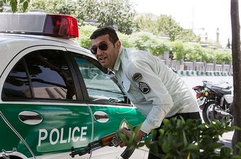 An Iranian policeman takes cover during an attack on the Iranian parliament in central Tehran, Iran, June 7, 2017.