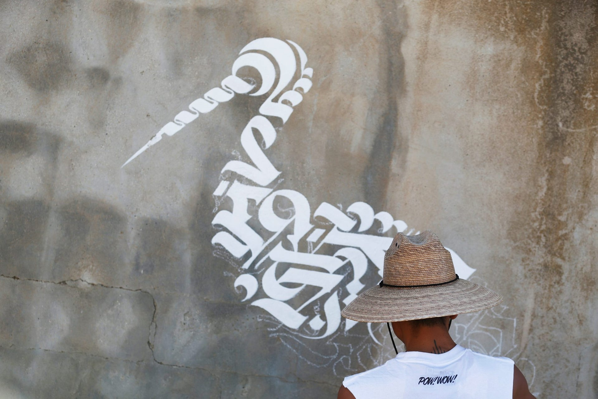 An American artist who goes by the name Cryptik works on his wall painting during POW! WOW! Israel in Arad, June 5, 2017.