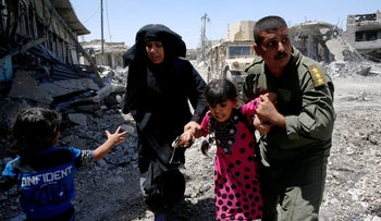 Iraqi soldiers help residents displaced by fighting between Iraqi forces and ISIS militants in Mosul's al-Zanjili's district, Iraq, June 7, 2017.