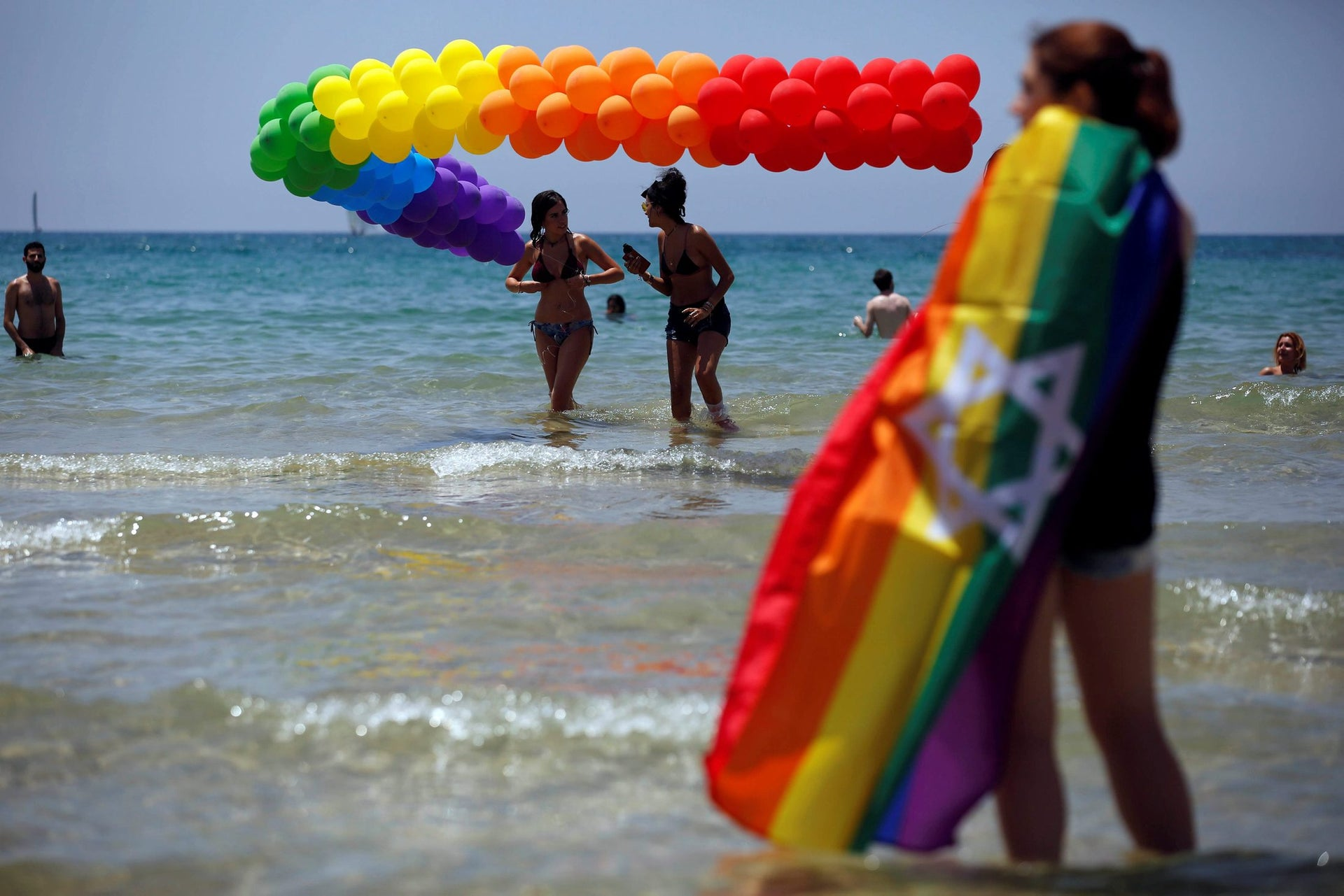 Revellers dip in the Mediterranean sea as they take part in a gay pride parade in Tel Aviv, Israel June 9, 2017.
