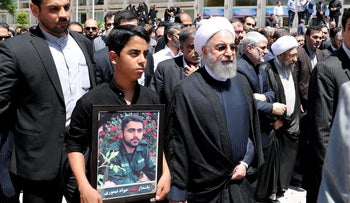 A handout picture provided by the Iranian Presidency on June 9, 2017 shows  Iran's President Hassan Rouhani walking alongside the relative of a victim of twin attacks in Tehran earlier in the week during a funeral in the capital.