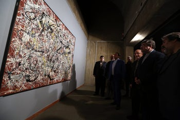 "Iranian Culture Minister Ali Jannati (2nd from R) looks at US artist Jackson Pollock's ""Mural on Indian Red Ground"" (1950) during the opening ceremony of an exhibition of modern art at Tehran's Museum of Contemporary Art (TMOCA) in the capital, on November 20, 2015. Some of the world's most expensive and rarely seen modern art, including works by the Americans Jackson Pollock and Andy Warhol, which are part of a collection bought in the 1970s by dealers acting for Farah, the wife of Shah Mohammad Reza Pahlavi, who fled into exile in 1979, heralding the country's Islamic revolution later that year, went on display in a major exhibition in Iran. AFP PHOTO / ATTA KENARE == RESTRICTED TO EDITORIAL USE, MANDATORY MENTION OF THE ARTIST UPON PUBLICATION, TO ILLUSTRATE THE EVENT AS SPECIFIED IN THE CAPTION == / AFP PHOTO / ATTA KENARE IRAN-CULTURE-ART STF"