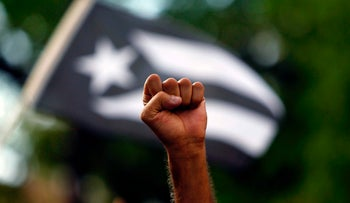 A man raises his fist in front of a black and white Puerto Rican flag during a protest against the referendum for Puerto Rico political status in San Juan, on June 11, 2017.