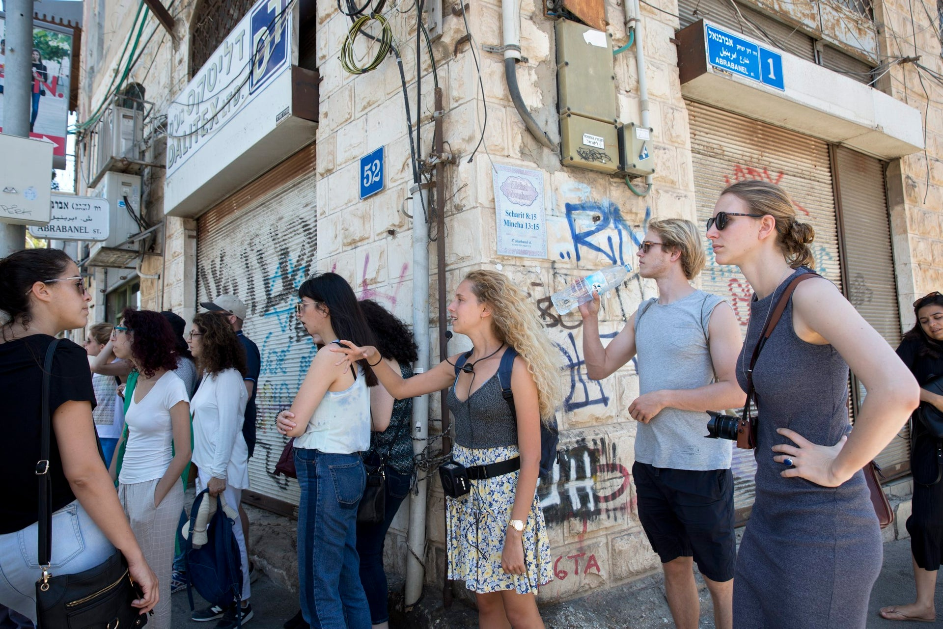 A guide talking to tourists on a corner in the Florentin neighborhood. This is just one of many groups in the area.