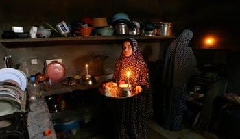 Palestinians prepare food at the kitchen of their house during a power cut in Khan Younis in the southern Gaza Strip June 12, 2017.