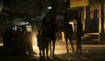 Palestinians walk on a street at the Al-Shati refugee camp in Gaza City during a power outage on June 11, 2017.