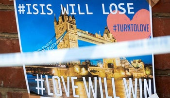 "A poster on a wall reads ""ISIS will lose; #Love will win"", at a police cordon near to Borough Market in London on June 5, 2017, left in tribute to the victims of the June 3 attacks"