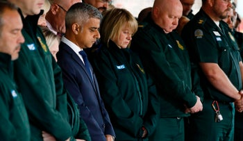 Sadiq Khan stands with ambulance paramedics as they pause for a minutes' silence in London on June 6, 2017, in memory of the victims of the June 3 terror attacks.