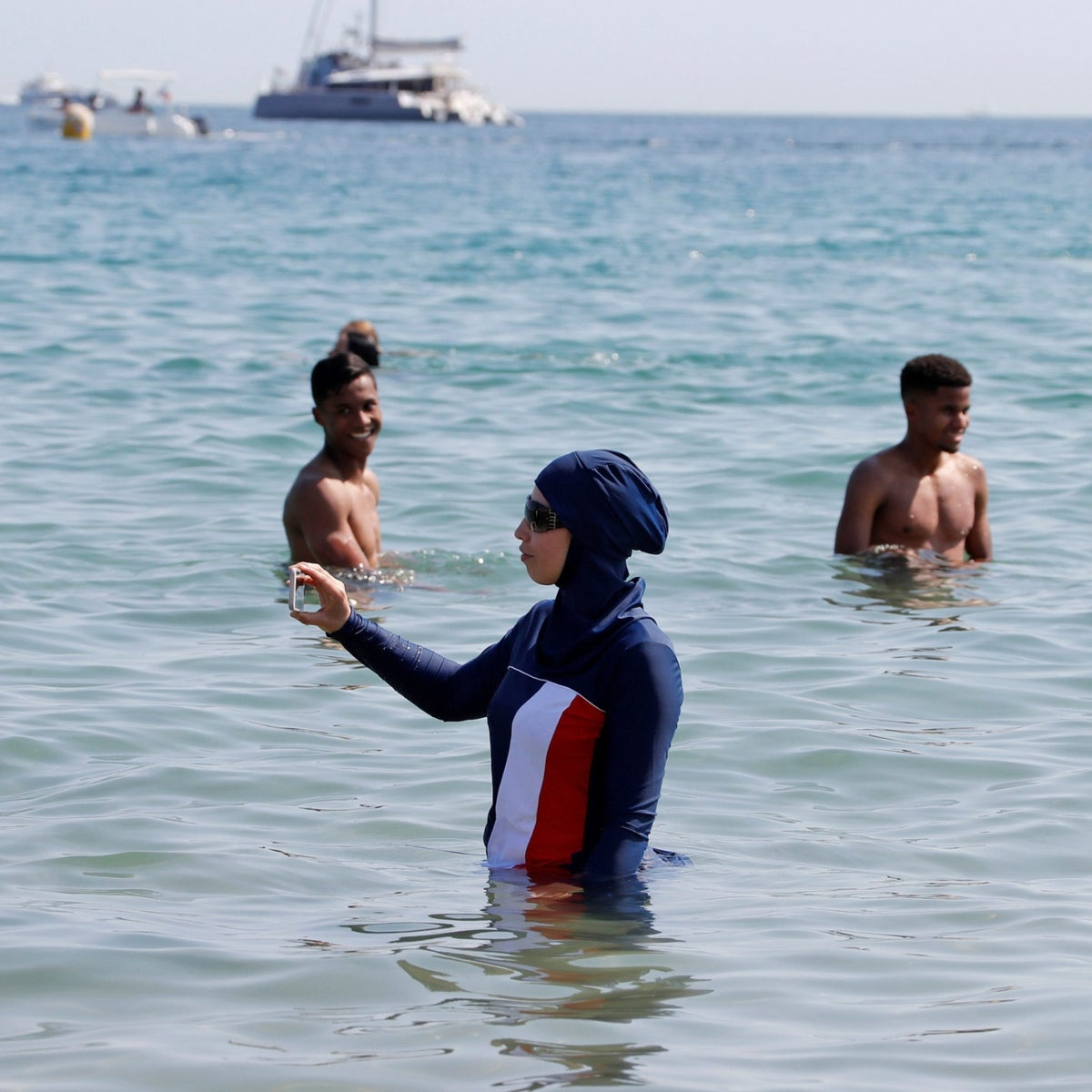 A woman wearing a burkini takes a selfie on the Cannes beach, May 27, 2017.
