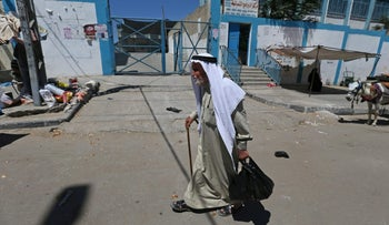 A Palestinian man walks past the United Nations food distribution center in Khan Younis in the southern Gaza Strip, June 11, 2017.