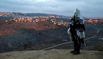 FILE PHOTO: A Jewish man covered in a prayer shawl near the West Bank outpost of Amona.