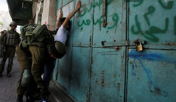 An Israeli soldier searches a Palestinian following a protest in support of Palestinian prisoners on hunger strike in Israeli jails, in the West Bank city of Hebron May 19, 2017.