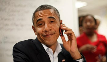 President Barack Obama reacts after realizing he dialed the wrong number while making calls from a local campaign field office during a unscheduled visit, Sunday, Oct. 28, 2012 in Orlando, Fla.