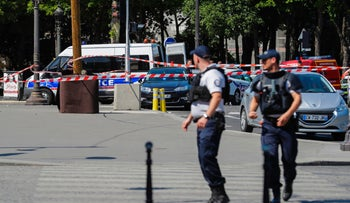 Police officers walk across a sealed off area on the Champs Elysees avenue in Paris, June 19, 2017.