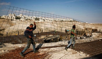 Workers carrying material at a construction site in the West Bank settlement of Ma'aleh Adumim, January 2017.