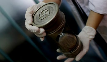 A member of the federal police holds an hourglass with Nazi markings at the Interpol headquarters in Buenos Aires, Argentina, Friday, June 16, 2017.
