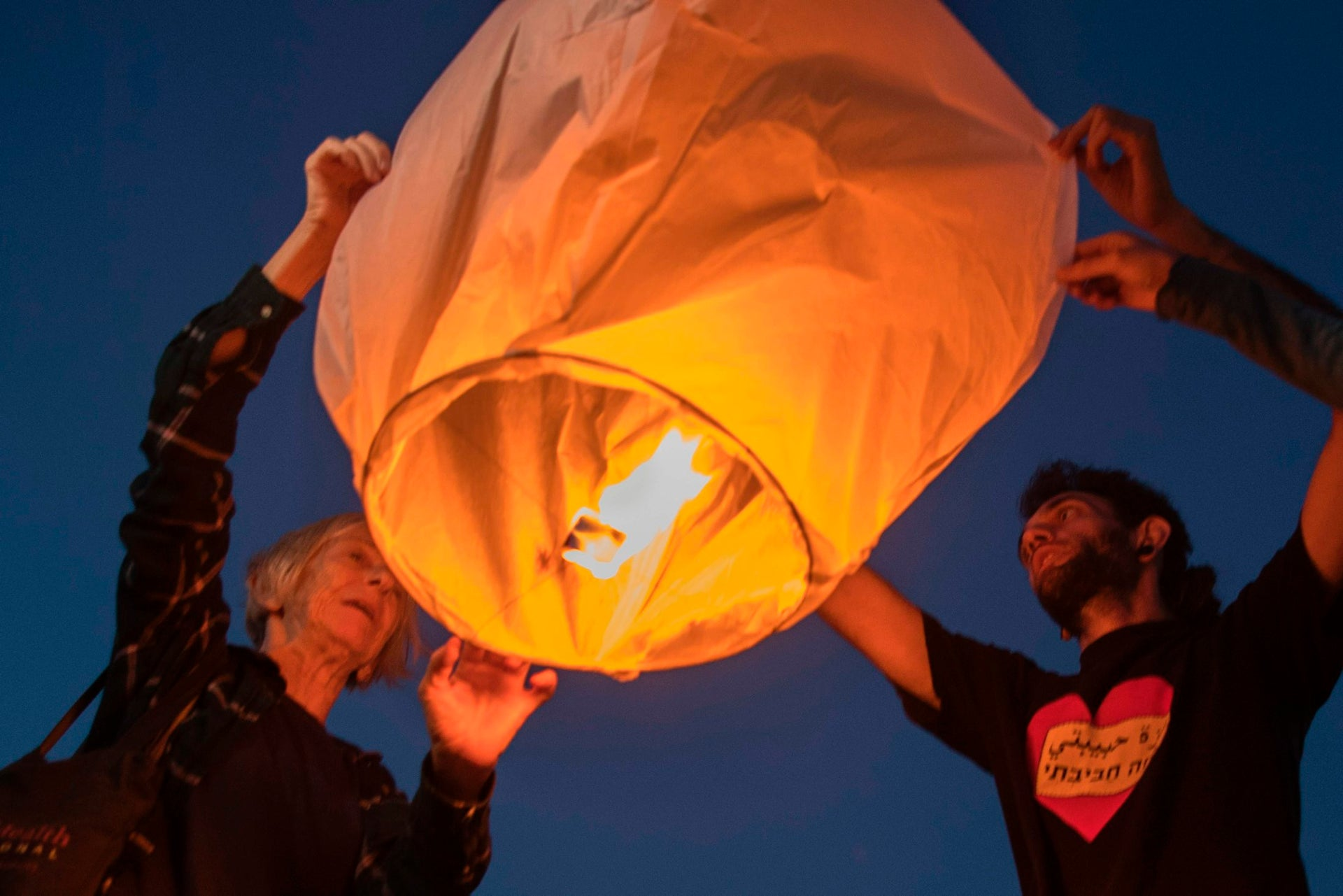 Israeli peace activists gather near the border fence with the Gaza Strip to launch into the air 150 sky paper lanterns in solidarity with Gaza residents on June 19, 2017, in the southern Israeli city of Ashkelon.
