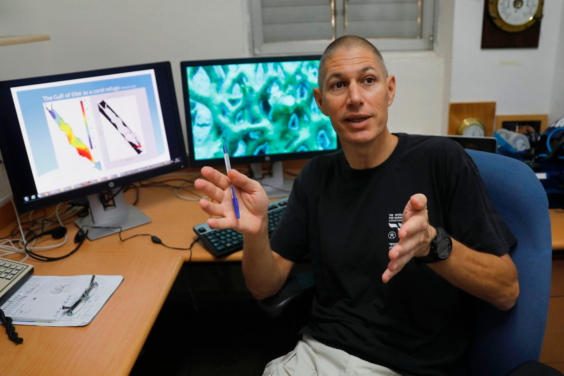 Maoz Fine, a professor of marine biology from Israel's Bar Ilan university who is conducting research on the Gulf of Eilat, gestures while sitting in an office at the Interuniversity Institute for Marine Sciences in the Red Sea resort of Eilat on June 12, 2017.