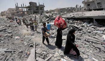 Palestinians carrying their belongings after salvaging them from their destroyed houses in the heavily bombed town of Beit Hanoun, Gaza Strip, August 1, 2014.