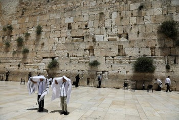 File photo: Men holding prayer shawls as they stand in front of the Western Wall, Judaism's holiest prayers site in Jerusalem's Old City May 17, 2017.