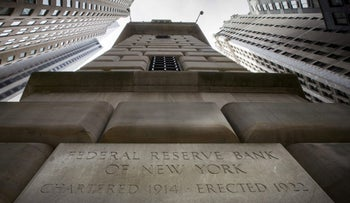 File photo: The corner stone of the New York Federal Reserve Bank is seen surrounded by financial institutions in New York City, New York, on March 25, 2015.