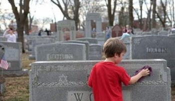 A youngster cleaning a headstone following an anti-Semitic attack on a Jewish cemetery in Minnesota, February 2017.