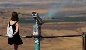 An Israeli tourist looks at the Syrian side of the border from Mount Bental, in the Israeli-occupied Golan Heights, a day after after projectiles fired from the war-torn country hit the Golan on June 25, 2017