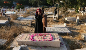 A Palestinian woman praying next to the grave of a relative on the first day of Id al-Fitr prayers, at a cemetery in Gaza City June 25, 2017.