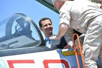 A handout picture released on June 27, 2017 Syrian President Bashar Assad sitting inside a Sukhoi Su-27 during his visit to the Hmeimim military base in Latakia province, Syria.