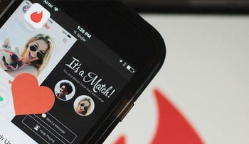 he Tinder Inc. application is displayed on a smartphone in an arranged photograph
