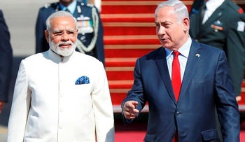 Israeli Prime Minister Benjamin Netanyahu (R) walks with his Indian counterpart Narendra Modi (L) during an official ceremoney at Ben-Gurion International airport