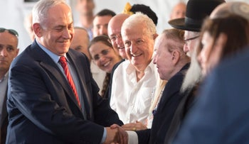 Israeli Prime Minister Benjamin Netanyahu, left, shaking hands with American Jewish casino tycoon Sheldon Adelson, at Ariel University in the West Bank, June 28, 2017.