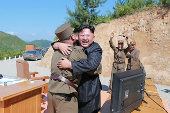North Korean leader Kim Jong Un reacts with scientists and technicians of the DPRK Academy of Defence Science after the test-launch of Hwasong-14 in this undated photo released by KCNA