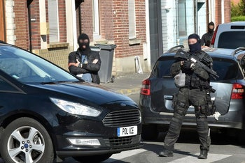 Police raiding an apartment building in northern France, July 5, 2017.
