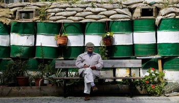 A man sits on a bench in front of the road block dividing a road in Nicosia, Cyprus' capital, April 10, 2017.