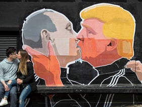 A couple kisses in front of graffiti depicting Russian President Vladimir Putin and U.S. President Donald Trump in Vilnius, Lithuania, in May 2016.