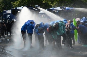 Police uses a water canon while demonstrators block a street during protests against the G-20 summit in Hamburg, Germany, July 7, 2017.