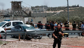 Security forces stand guard at the site where a Palestinian attempted a car ramming and knife attack against soldiers at a junction in Tekoa on July 10, 2017.